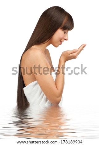 Young beautiful woman with long brown hair washing her face by fresh water, against white background - stock photo