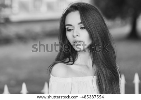 Young beautiful woman with long brunette hair. Calm girl with perfect clean skin posing in park