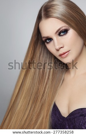 Young beautiful woman with long hair and false eyelashes - stock photo