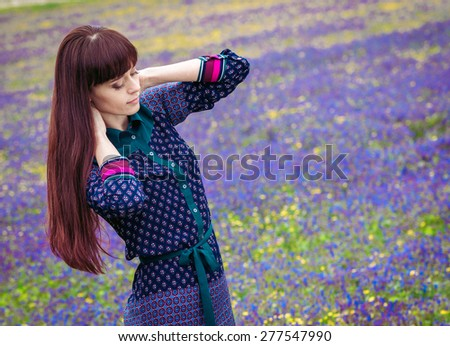 Young beautiful woman with long hair in spring field - stock photo