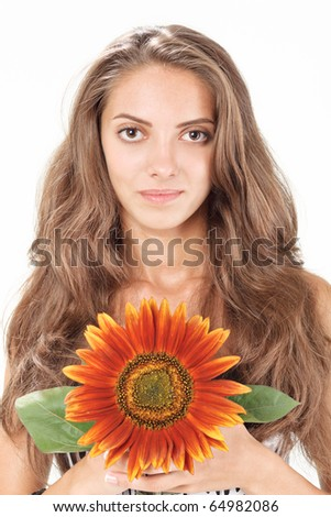 Young beautiful woman with long hairs holding sunflower near face