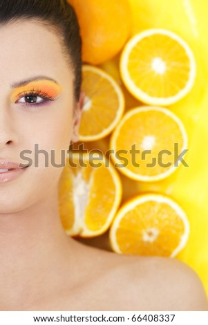 Young beautiful woman with oranges on background - stock photo