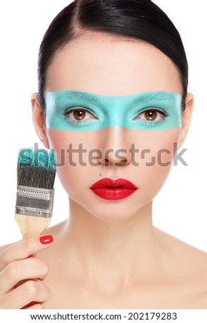 Young beautiful woman with painting brush and paint on her face over white background