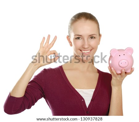 Young beautiful woman with piggy bank (money box) and showing ok, isolated on white background