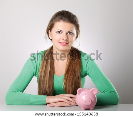 Young beautiful woman with piggy bank (money box), isolated on grey background - stock photo