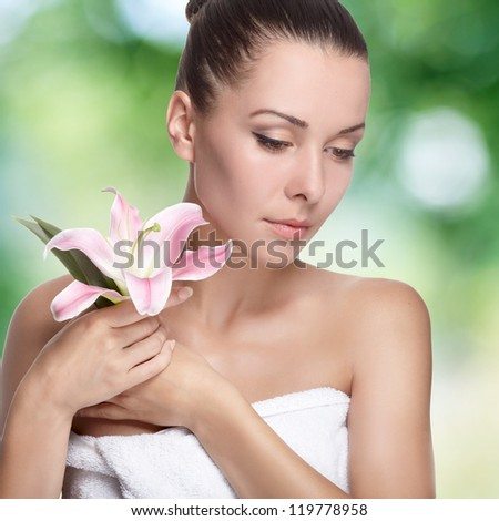 young beautiful woman with pink flower. On background