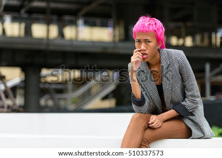 Young beautiful woman with pink hair sitting in city