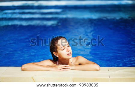 Young beautiful woman with pleasure in swimming pool in sunny day