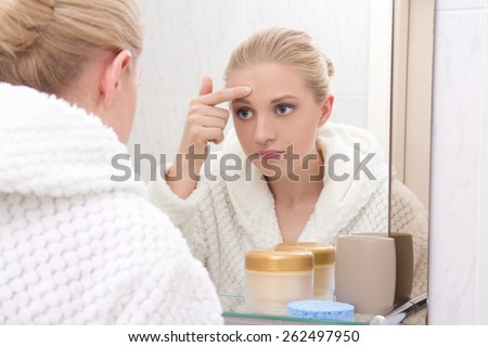 young beautiful woman with problem skin looking at mirror in bathroom - stock photo