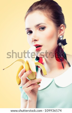 Young beautiful woman with red glamour lips and eye arrow make-up wearing fancy plastic earrings and eating banana, on yellow background, pin-up style - stock photo