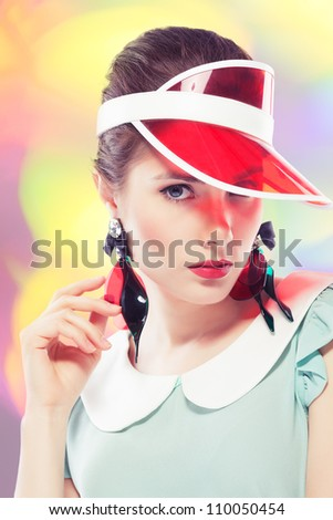 Young beautiful woman with red glamour lips and eye arrow make-up wearing fancy plastic earrings and red sun visor on multicolor background, retro styled beauty - stock photo