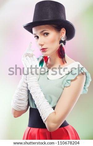 Young beautiful woman with red glamour lips and eye arrow make-up wearing fancy plastic earrings, top hat and white formal gloves, on colored background, retro style - stock photo