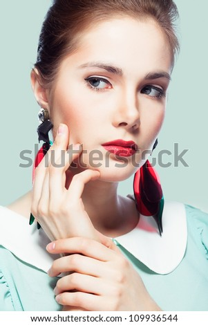 Young beautiful woman with red glamour lips and eye arrow make-up wearing fancy plastic earrings on blue background, retro styled beauty - stock photo