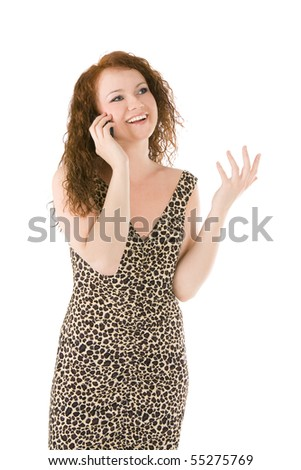 Young beautiful woman with red hair in dress talks on a cell phone, isolated on white background. - stock photo