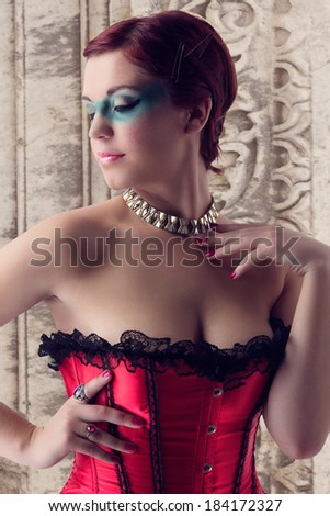 young beautiful woman with red hair wearing red satin and lace corset on architectural background