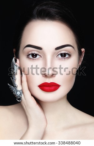 Young beautiful woman with red lipstick and fancy claw ring on her finger - stock photo