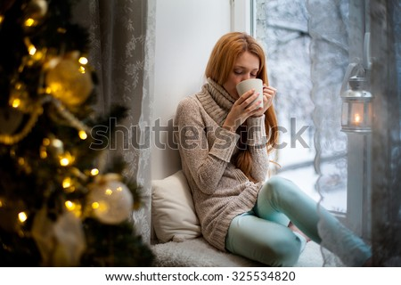Young beautiful woman with reddish hair sitting home by the window with cup of hot coffee wearing knitted warm sweater. Christmas tree with decorations and lights in the room, snowy winter outside - stock photo