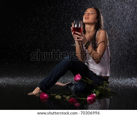 Young beautiful woman with roses and glass of wine sits under rain on a black background. - stock photo