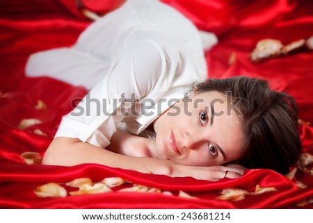 Young beautiful woman with roses leaves, lying on red satin, representing beauty concept  - stock photo