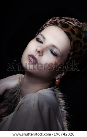 Young beautiful woman with scarf on the head posing in studio on the black background
