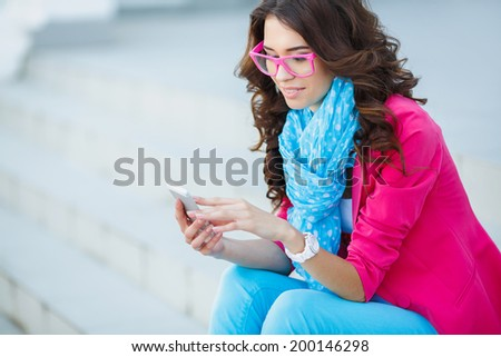 Young beautiful woman with smartphone - outdoor lifestyle portrait - stock photo