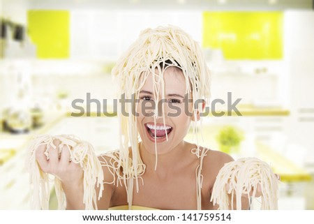 Young beautiful woman with spaghetti noodles on her hairs - stock photo