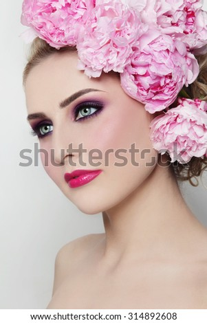 Young beautiful woman with stylish make-up and peonies in her hair - stock photo