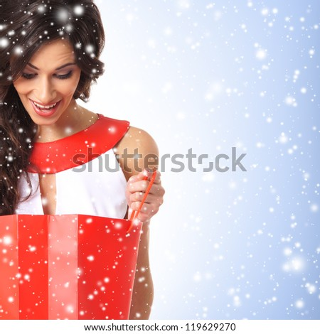 Young beautiful woman with the shopping bag over the Christmas background - stock photo