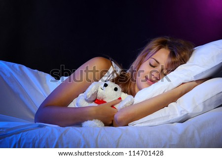 young beautiful woman with toy rabbit sleeping on bed in bedroom - stock photo