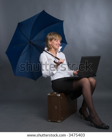young beautiful woman with umbrella, suitcase and laptop - stock photo