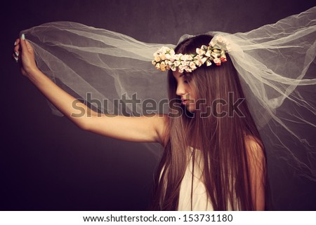 young beautiful woman with veil and wreath of flowers, profile, studio shot - stock photo