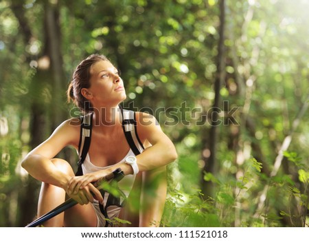 Young beautiful woman with walking sticks in a forest, having a break - stock photo