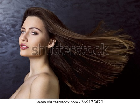 Young beautiful woman with wind in her brown long hair.