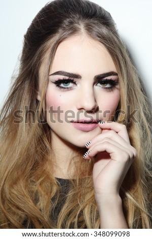 Young beautiful woman with winged eye make-up and stylish hairdo - stock photo