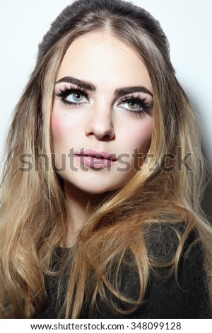 Young beautiful woman with winged eye make-up and stylish hairdo looking upwards - stock photo