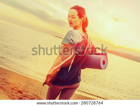 Young beautiful woman with yoga mat standing on beach in summer at sunset and ready for workout. Image with sunlight effect - stock photo