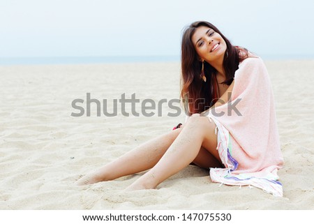 Young beautiful woman wrapped herself with blanket on the beach - stock photo