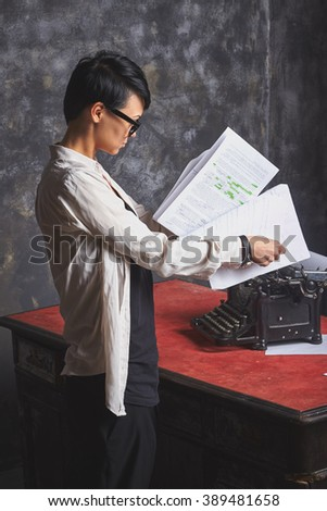 Young  beautiful woman writer in creative process, reading her work, writing article, art space with grey background and retro typewriter - stock photo