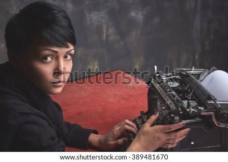 Young beautiful woman writer in dark wear, sitting in art space, creative process on retro typewriter, dark background - stock photo