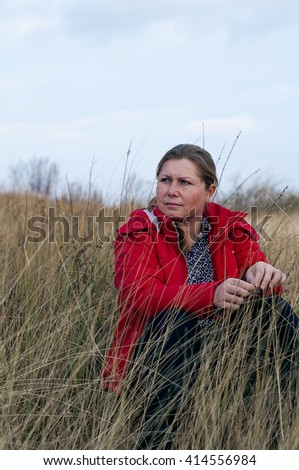Young beautiful woman 40 years old posing in red jacket outdoors. Portrait of a woman outdoors - stock photo
