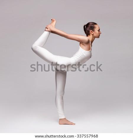 young beautiful woman yoga posing isolated over grey studio background - stock photo