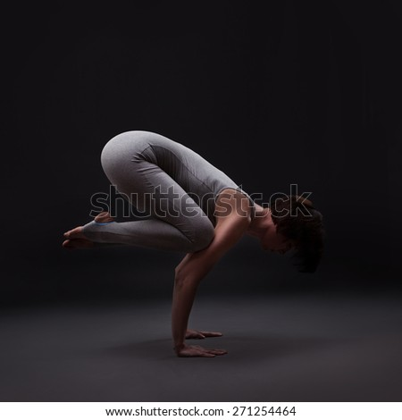 young beautiful woman yoga posing on a black studio background - stock photo