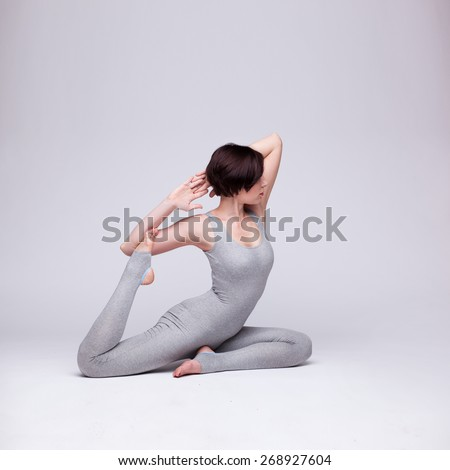 young beautiful woman yoga posing on a grey studio background - stock photo