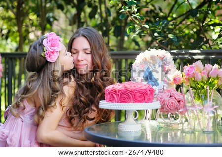 Young beautiful women and her daughter celebrate birthday party with a cake outdoor - stock photo