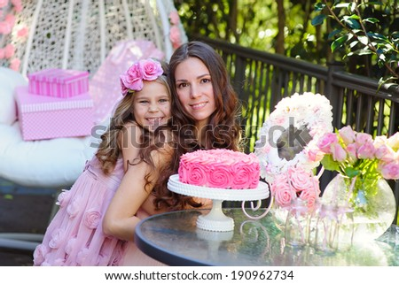 Young beautiful women and her daughter celebrate birthday with a cake - stock photo