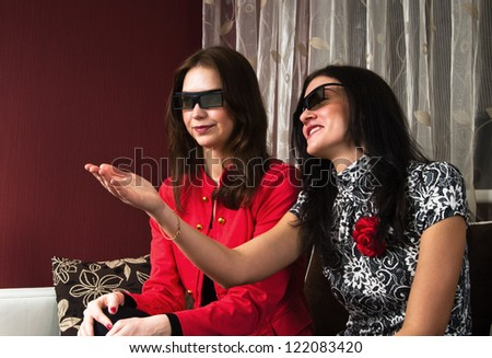 young beautiful women at home watching a 3D movie - stock photo