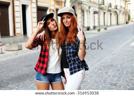 Young beautiful women at the weekly cloth market - Best friends sharing free time having fun and shopping in the old town in a sunny day - stock photo