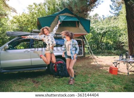 Young beautiful women friends having fun in a campsite - stock photo