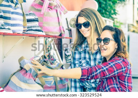 Young beautiful women girlfriends at flea market looking for bags - Best friends sharing free time having fun and shopping during travel - Soft vintage marsala filtered look - Focus on smallest girl - stock photo