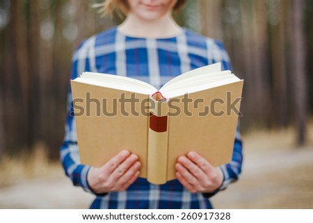 young beautiful women holding open book in hands - stock photo